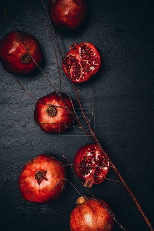 top view of ripe pomegranates and twig arrangement on black surface