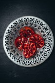 top view of fresh cut garnets in metal bowl on black surface