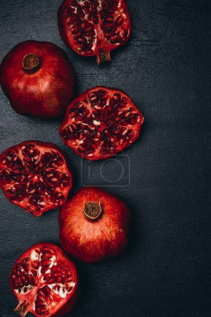 Photo for Top view of ripe pomegranates arrangement on black surface - Royalty Free Image