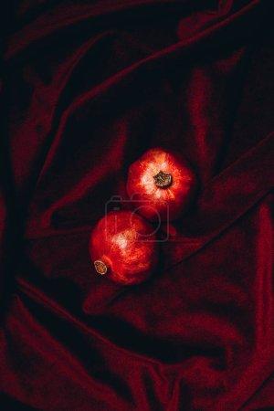 Photo pour Vue de dessus des grenades mûres sur fond de tissu de velours rouge - image libre de droit