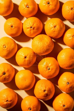 Photo for Top view of arranged fresh wholesome tangerines on beige background - Royalty Free Image