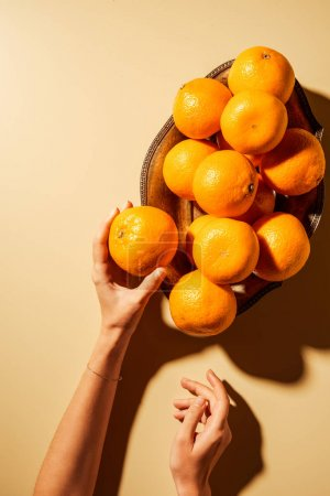 Cropped shot of woman holding tangerine on beige background with metal bowl