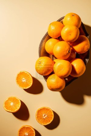 Flat lay with tangerines in metal bowl on beige backdrop