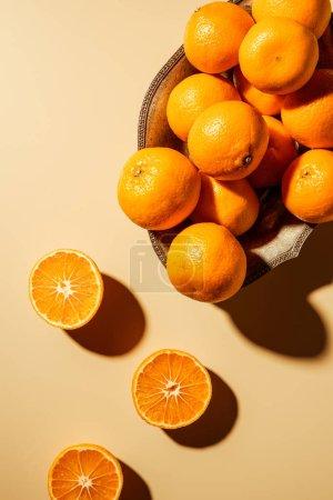 Photo pour Plat poser avec les mandarines en bol en métal sur fond beige - image libre de droit