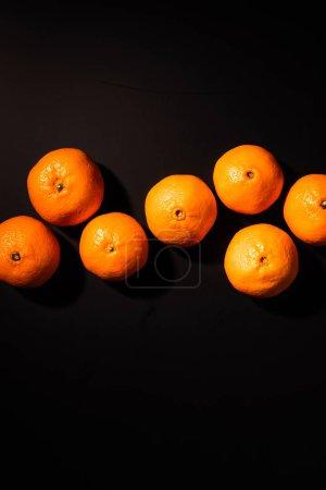 Foto de Vista superior del arreglo de mandarinas saludables sobre fondo negro - Imagen libre de derechos