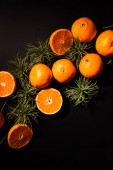 top view of fresh tangerines and green plants arranged on black tabletop