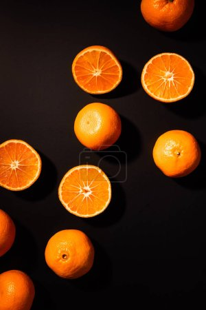 top view of arrangement of wholesome and cut tangerines on black background