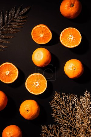 top view of fresh tangerines and decorative golden twigs arranged on black tabletop