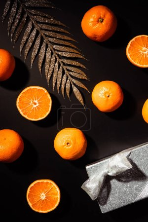 top view of fresh tangerines, decorative twig and gift box on black background