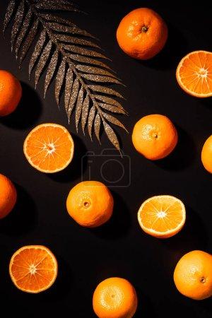 Photo pour Lay plat avec mandarines fraîches et décoratif brindille doré sur le dessus de table noir - image libre de droit