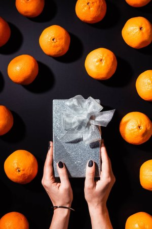 Photo for Partial view of woman holding silver gift box on black tabletop with fresh tangerines around - Royalty Free Image