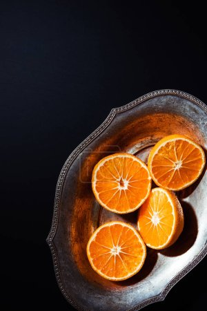 Photo for Top view of mandarins and metal bowl on black backdrop - Royalty Free Image