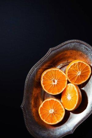 Photo pour Vue de dessus des mandarines et bol en métal sur fond noir - image libre de droit