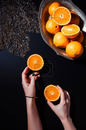 partial view of woman holding halves of mandarin on black surface with decorative silver  twig and tangerines in metal bowl