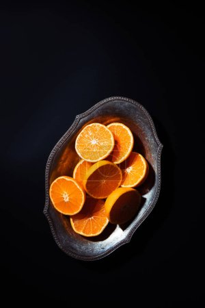 Photo for Top view of cut mandarins halves in metal bowl on black tabletop - Royalty Free Image