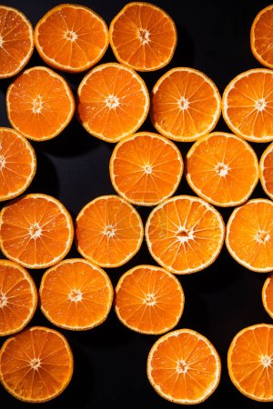 Photo for Full frame of arranged cut tangerines halves on black background - Royalty Free Image