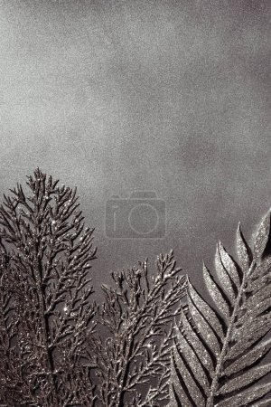 top view of shiny decorative silver twigs on grey background
