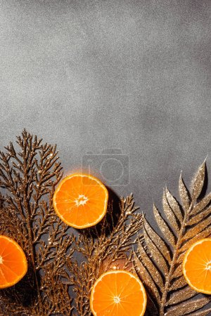 flat lay with fresh tangerines and decorative golden twigs on grey backdrop