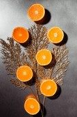 flat lay with arranged mandarins halves and golden twig on grey backdrop