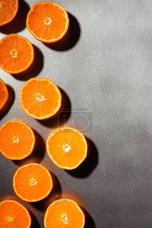 flat lay with arranged mandarins halves on grey background