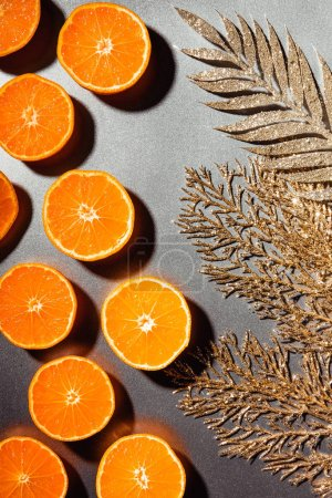 Photo for Flat lay with fresh tangerines and golden twigs on grey backdrop - Royalty Free Image
