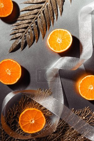 flat lay with fresh tangerines, silver ribbon and decorative golden twigs on grey backdrop