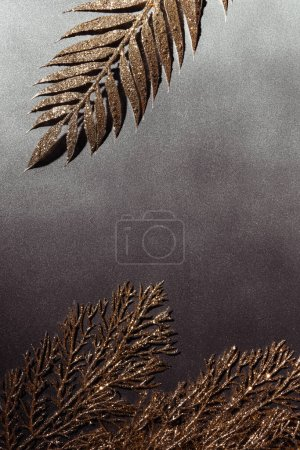 top view of shiny decorative golden branches arranged on grey backdrop