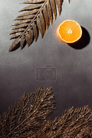 top view of cut tangerine half and decorative golden twigs on grey background