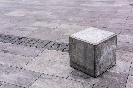 close up view of grey stone cube at urban street