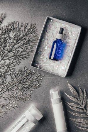 Photo pour Vue surélevée du coffret cadeau de Noël avec sérum, lotion, eau micellaire, branches décorées sur argent - image libre de droit