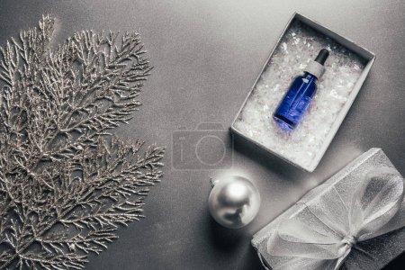 Blick von oben auf Serum in Geschenkbox und Weihnachtskugel mit Tannenzweigen auf Silber