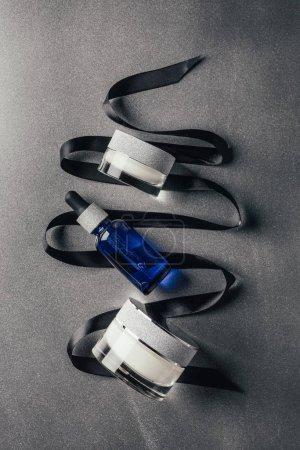 Photo pour Vue de dessus de crème de beauté, sérum avec un ruban noir sur argent - image libre de droit