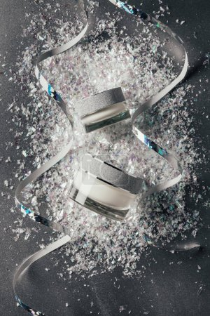 Photo for Elevated view of festive ribbons and beauty cream with decorated shavings on silver - Royalty Free Image