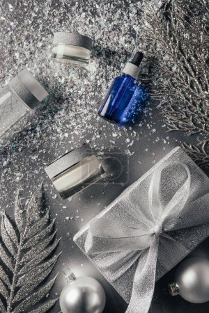 Photo for Elevated view of composition with beauty cream, serum, micellar water and christmas decorations on silver - Royalty Free Image