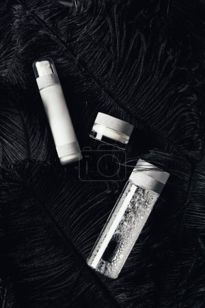 top view of beauty cream, micellar water and lotion on surface with black feathers