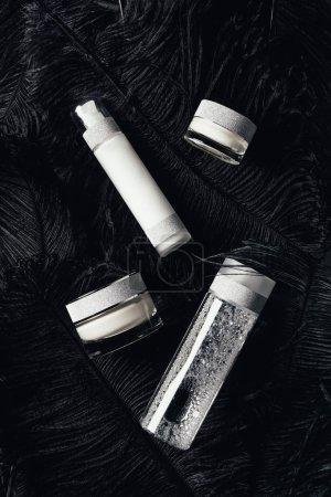 Photo pour Vue d'en haut de la crème de beauté, eau micellaire et lotion sur surface avec plumes noires - image libre de droit