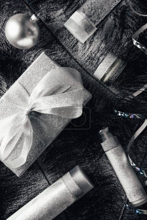 elevated view of christmas ball, gift box and beauty treatment equipment on surface with black feathers covered by silver
