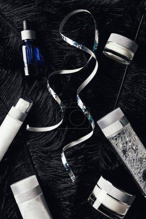 Photo pour Vue d'en haut sur ruban, eau micellaire, sérum, crème de beauté sur la surface avec des plumes noires - image libre de droit