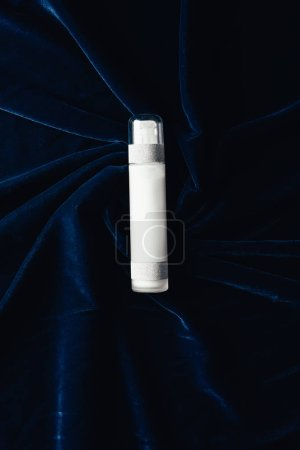 top view of beauty lotion on velvet surface