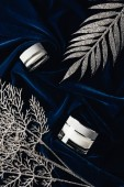 top view of beauty cream between silver decorated branches on velvet surface