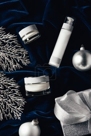 Photo for Elevated view of gift box, beauty cream, lotion and silver christmas balls on velvet surface - Royalty Free Image