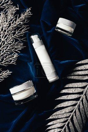 Photo pour Vue du dessus de la lotion et la crème entre les branches de Noël argent à surface velours beauté - image libre de droit