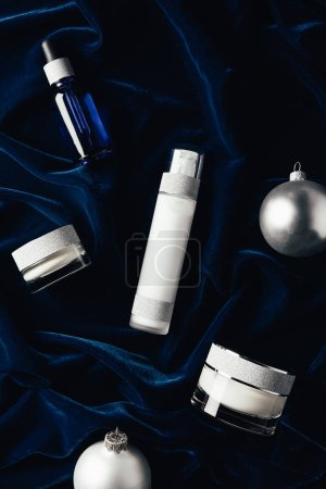 Photo for Flat lay with beauty cream,serum, lotion and silver christmas balls on velvet surface - Royalty Free Image