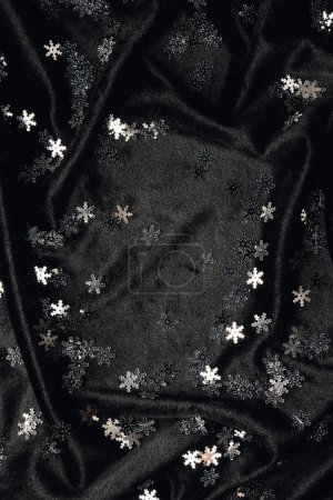festive background with shiny decorative silver snowflakes on black fabric