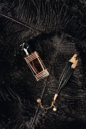 top view of perfume bottle and decorative black feathers with golden dust