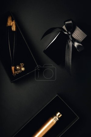 top view of bottled perfumes and decorative feathers on black