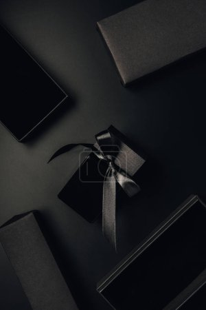 Photo for Top view of black perfume bottle with bow and boxes on black - Royalty Free Image