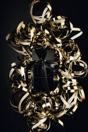 close-up view of black perfume bottle with bow and shiny golden ribbons on black