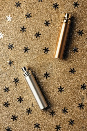 top view of golden and silver perfume bottles and decorative snowflakes