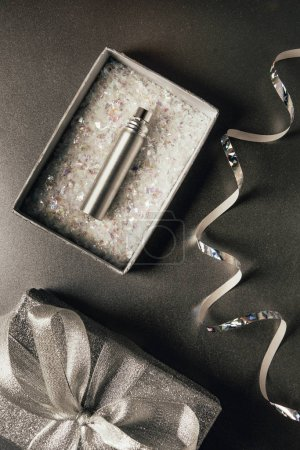 top view of perfume bottle in gift box and shiny silver ribbon on grey